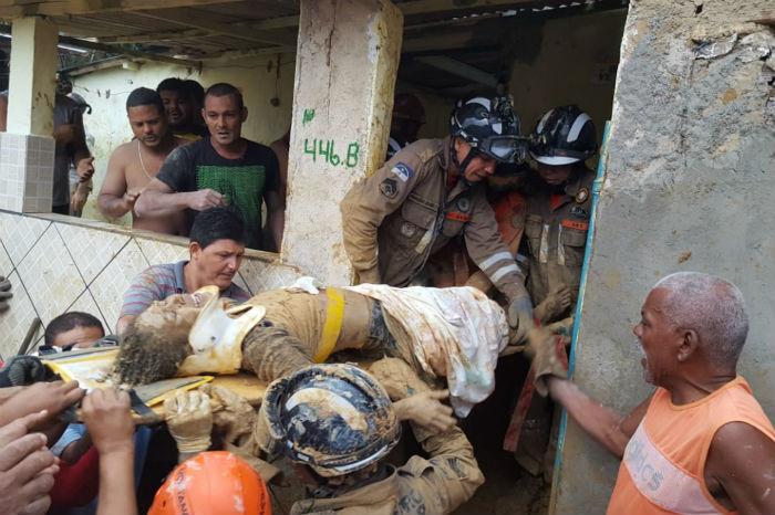 Agentes da Defesa Civil, do Corpo de Bombeiros e voluntários trabalham no local onde um homem morreu e outras ficaram desaparecidas após o deslizamento de uma barreira em Camaragibe. Foto: Bruno Lafaiete/Código19/Agência Estado.