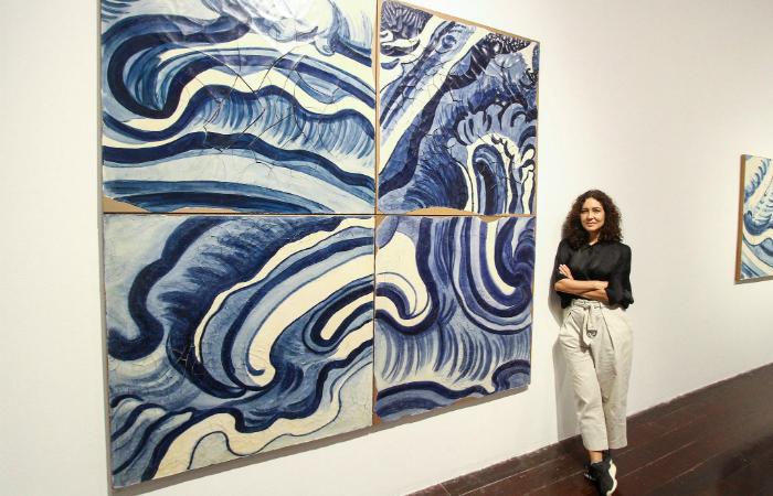 """Artista ao lado de obra mais """"geométrica"""". Peça pertence à cantora Marisa Monte. Foto: Bruna Costa/DP"""