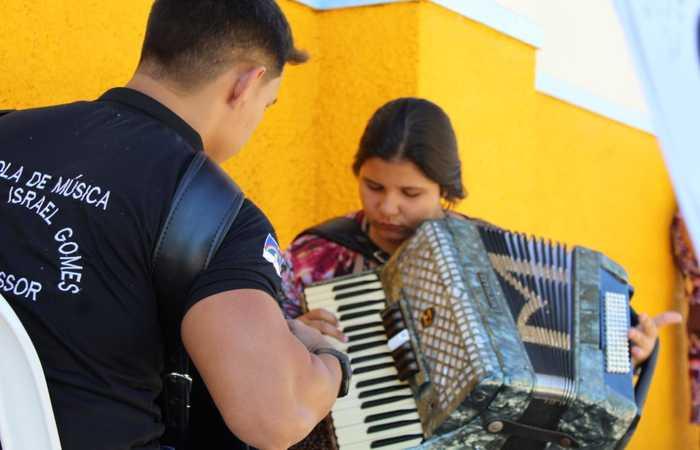 Eder Ramalho ensina a aluna Maria Vitória Rodrigues de Oliveira a tocar sanfona. Foto: Divulgação