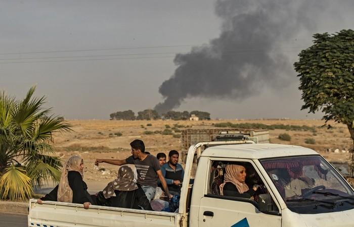 Civis andam em uma caminhonete enquanto a fumaça sobe após bombardeio turco na cidade de Ras al-Ain, no nordeste da Síria e fronteira com a Turquia - Foto: Delil SOULEIMAN / AFP.