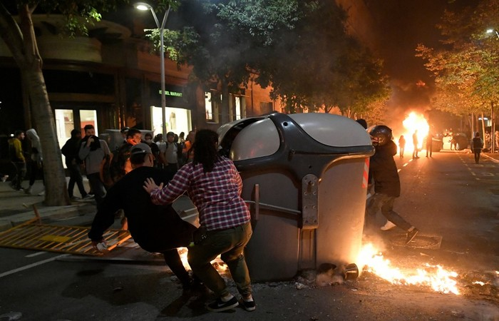 Português Protesters burn garbage containers during protests in Barcelona on October 15, 2019,   Aprenda a pronunciar Manifestantes queimam contêineres de lixo durante protestos em Barcelona - Foto: LLUIS GENE / AFP.