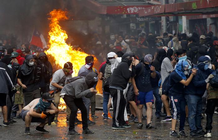 Ao passar diante do Palácio Presidencial, os manifestantes gritaram palavras de ordem contra o Piñera e insultaram os policiais que protegiam o La Moneda (Foto: JAVIER TORRES / AFP)