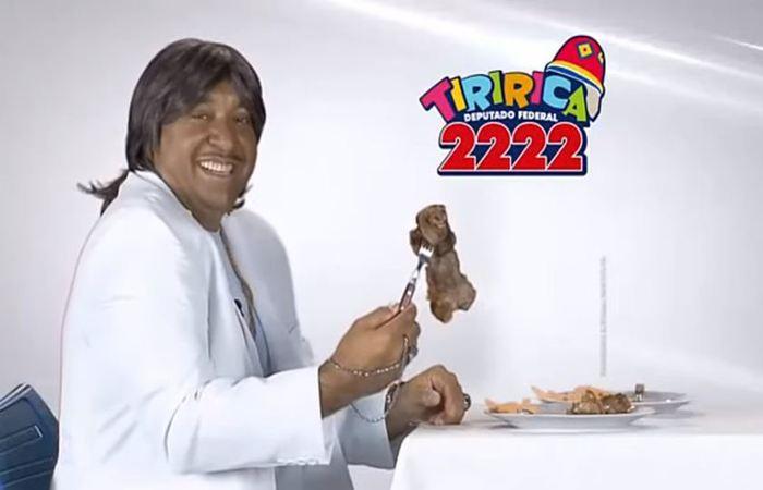 """Tiririca fez uma paródia da música - """"O Portão"""" - e da cena, cantando de branco, em frente a um piano e um prato de carne, que """"Brasília é seu lugar"""". (Foto: Reprodução/Youtube)"""