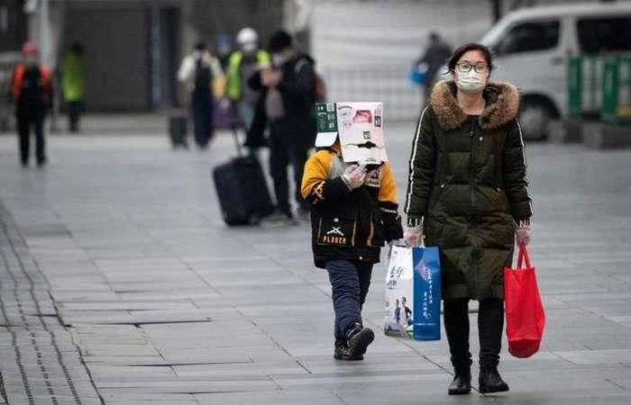 Menino com caixa na cabeça para se proteger do COVID-19, em Xangai: nova metodologia de diagnóstico permitirá tratamento mais cedo (Foto: AFP / NOEL CELIS)
