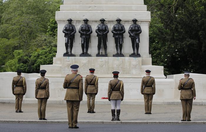 Oficiais britânicos em frente à estatuas de soldados, com 2 metros de distância, para celebrar o fim da 2ª Guerra. (Foto: Tolga AKMEN / AFP)