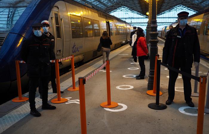 Agentes esperam para verificar os viajantes em busca de passagens e respeitar as medidas higiênicas antes de embarcarem no trem na principal estação ferroviária (Foto: Guillaume Souvant/AFP)