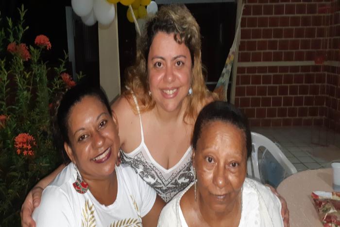 A jornalista Aline Moura (centro) foi diagnosticada com Covid-19. A sogra dela (direita) morreu por Síndrome Respiratória Aguda Grave.  (Foto: Arquivo Pessoal)