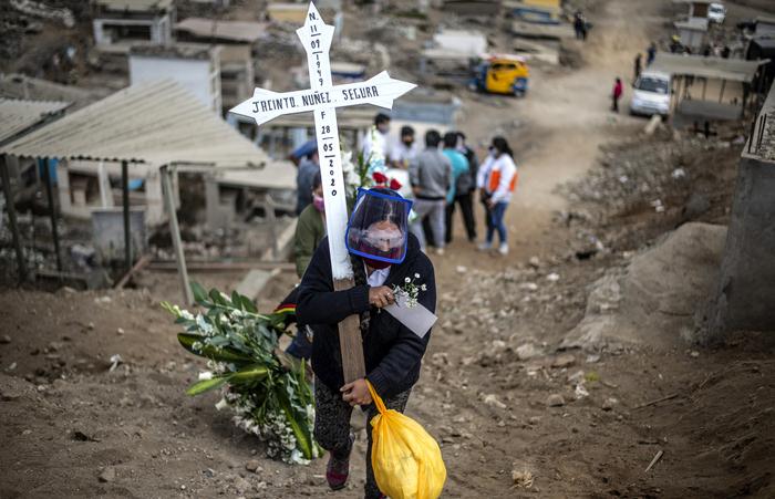 Parente de uma vítima da Covid-19 carregando uma cruz em cemitério de Lima, no Peru (Foto: Ernesto Benavides/AFP)