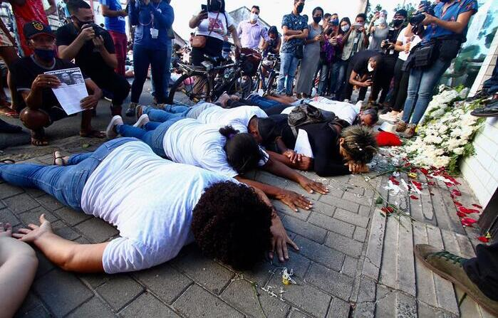 Familiares deitados na calçada do condomínio (Foto: Bruna Costa/Esp. DP)