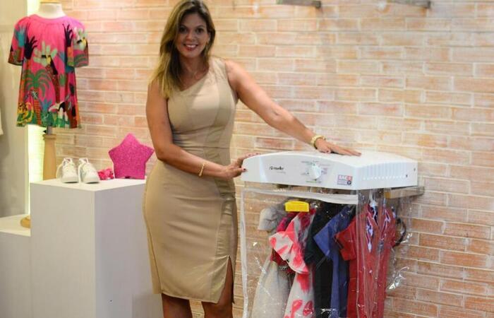 Nova máquina de higienização da Vila Kids e a proprietária da loja, Isis lopes. (Crédito: Gabriel Pontual/Divulgação   )