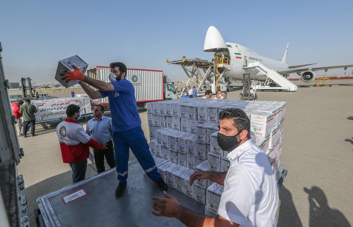 Trabalhadores do Crescente Vermelho Iraniano carregam um avião com ajuda ao povo libanês na pista do aeroporto de Mehrabad, na capital Teerã (Foto: Atta Kenare/AFP)