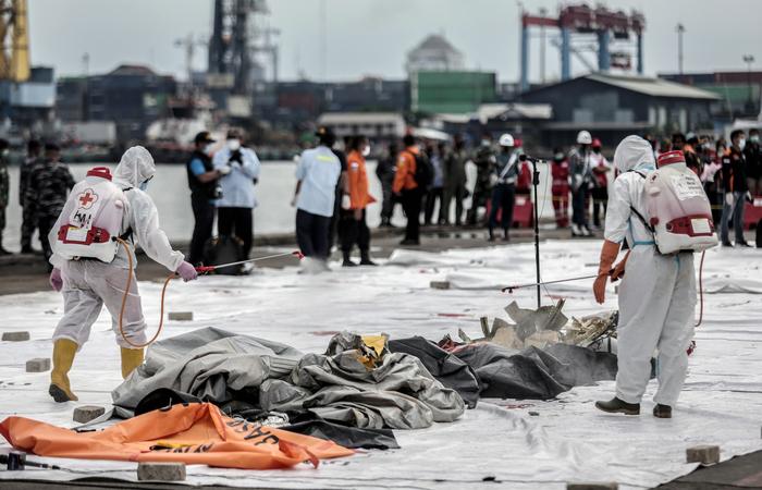 Horas antes, equipes de mergulhadores encontraram partes de corpos, destroços da fuselagem da aeronave e roupas dos passegeiros (Foto: ADITYA AJI / AFP )