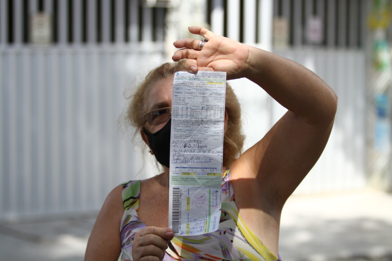 A moradora Marilene de Melo mostra a conta de água  (Foto: Peu Ricardo/Esp.DP)
