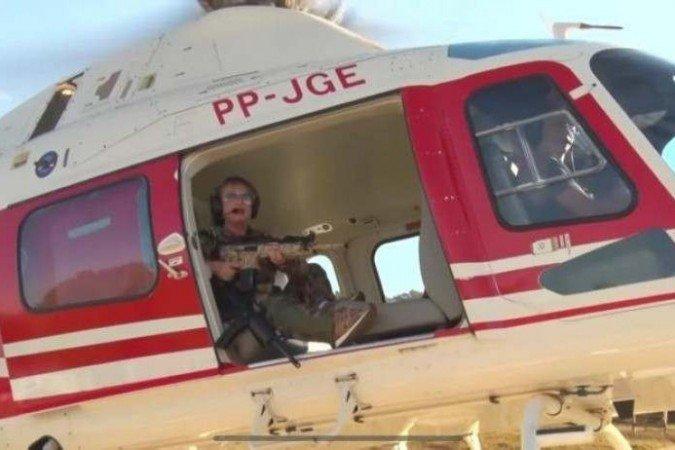 (Vídeo feito por Magda Moffato, que segura rifle e embarca em helicóptero atrás do foragido, foi considerado deboche contra policiais. Foragido é buscado por mais de 200 soldados. Foto: Reprodução/Facebook )