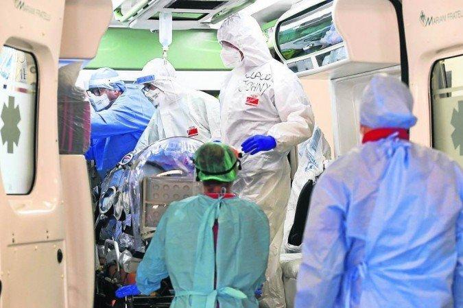 (Equipe de hospital em Milão retira paciente infectado pelo Sars-CoV-2 de ambulância: após restabelecimento, 16% têm sinais depressivos. Foto: Miguel Medina/AFP )