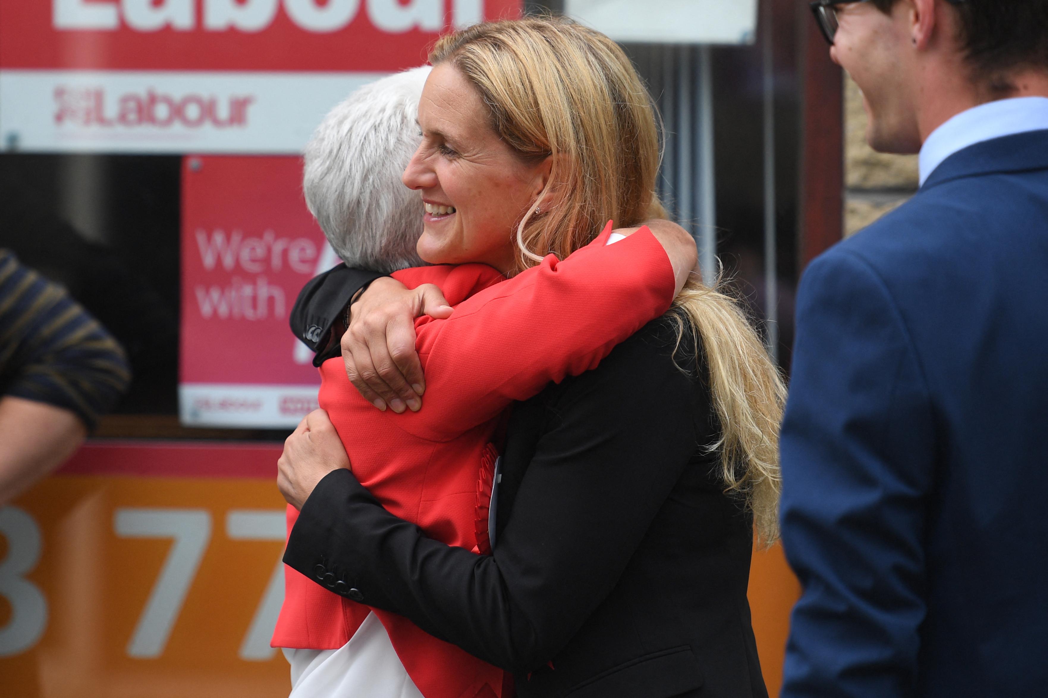Kim Leadbeater, do Partido Trabalhista, abraça sua mãe, Jean Leadbetter, do lado de fora da sede da campanha em Cleckheaton (Foto: Oli SCARFF / AFP)