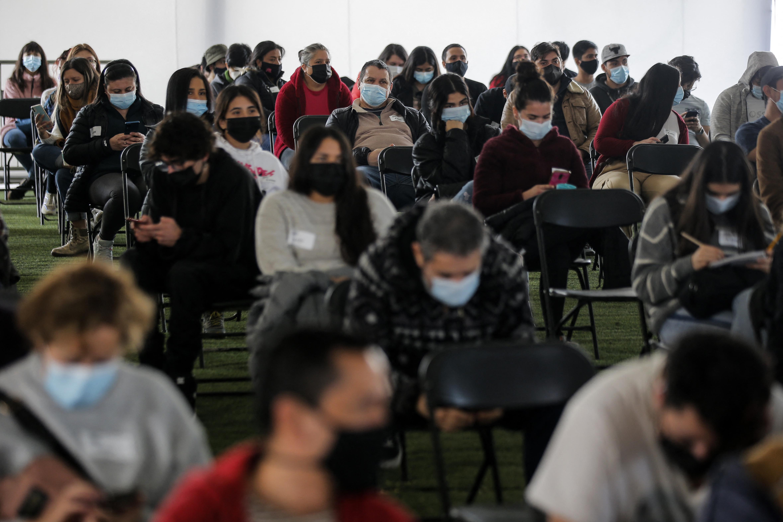 (População chilena esperando para tomar a vacina da Pfizer contra Covid-19 no centro de vacinação em Santiago. Foto: JAVIER TORRES / AFP)