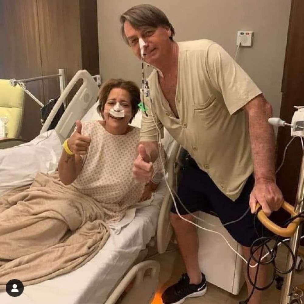 (Uma foto postada nas redes sociais pela primeira-dama, Michelle Bolsonaro, mostra o mandatário de pé, posando ao lado de outra paciente, enquanto se apoia em um suporte de sonda. Foto: Reprodução / Redes Sociais)