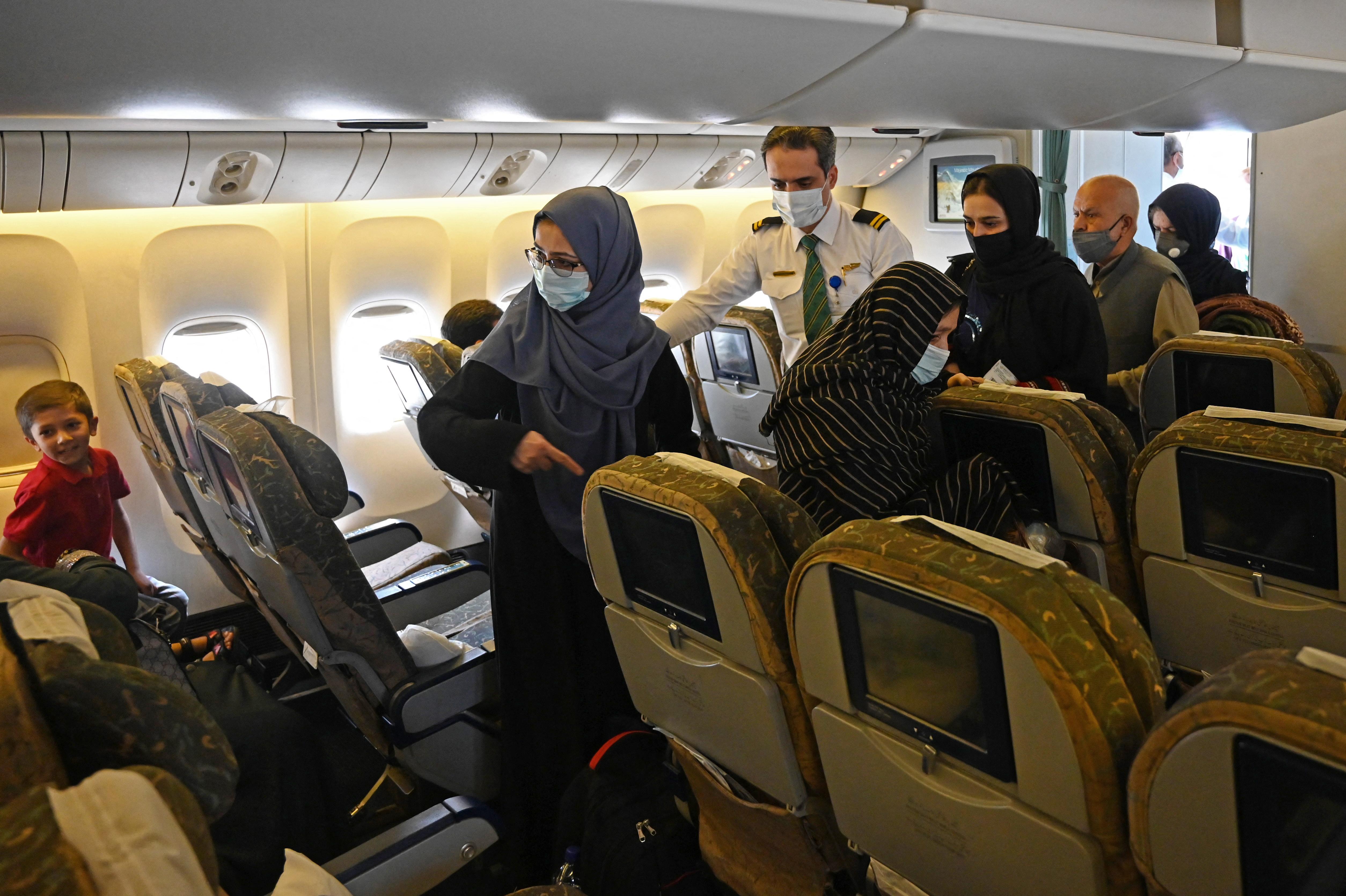 Passageiros a bordo do primeiro voo comercial partindo do aeroporto de Cabul desde a volta do Talibã ao poder (Foto: Aamir QURESHI / AFP)