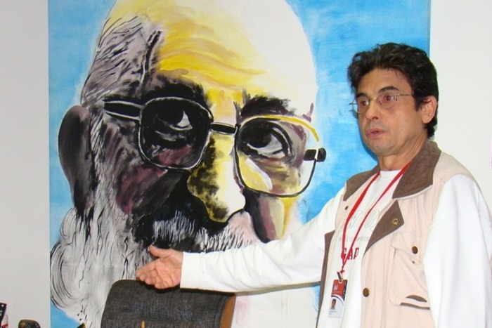 Lutgardes Costa Freire, filho caçula de Paulo Freire, ao lado de uma pintura do pai (Foto: Instituto Paulo Freire)